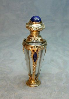 vintage French perfume scent bottle cast in chased sterling silver with inlaid Lapis Lazuli lozenges and button on the lid. vintage French perfume scent bottle cast in chased sterling silver with inlaid Lapis Lazuli lozenges and button on the lid.