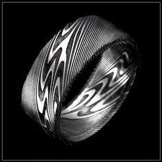 Thor Damascus Steel Men\'s Wedding Ring. Andrew Nyce Designs offers this unique contemporary metal men\'s wedding band composed of distinctive swirling layers of Damascus stainless steel with the Thor pattern and a black oxide coating.