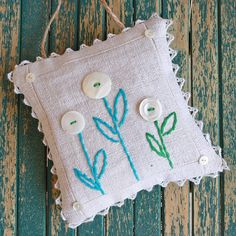 button flowers with embroidered stems on a sachet