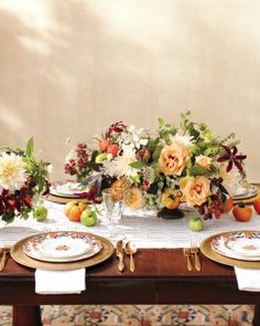 Summery Tablescape -- These centerpieces were created by anchoring dahlias, hydrangeas, roses, scabiosa, and clematis vines in urns, then strategically mixing in beets, raspberries, and fresh herbs. Heritage tomatoes scattered along an eyelet runner bring an extra punch of color and a summer-harvest feel, while vintage plates and brass flatware add to the charm.