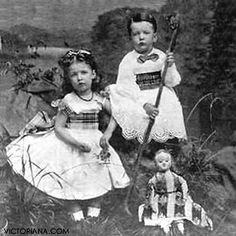 Boy and girl pose with antique doll, c 1860s.