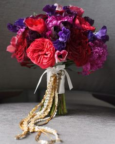 Jewel-toned English cabbage roses, peonies, and sweet peas were joined with gold and white ribbons for this bouquet that Dani carried for her New Year's wedding in Chicago. A key to the door of Dani's grandparents' first house dating back to the 1930s was tied on as a sentimental addition.