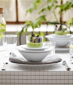 Ein Esstisch, der mit weißen IKEA 365+ Tellern aus Feldspatporzellan, Gläsern und Besteck aus Edelstahl gedeckt ist.