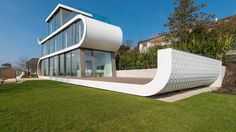 The home's curving white facade arcs and lengthens to give the structure a playful, sled-like look.