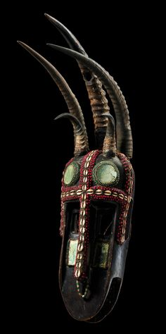 Africa | Mask from the Bamana/Bozo people of the Kita region of Mali | Wood, resin-like mass, cowrie shells and abrus seeds, mirror glass, glass beads and five animal horns | ca. 1978
