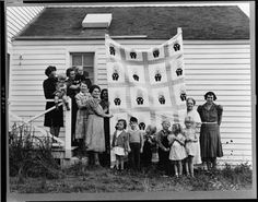 Photo by Dorothea Lange -- Women display an Overall Bill quilt, likely a group project