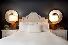 love the design of the upholstered headboard and mirrors behind the table lamps