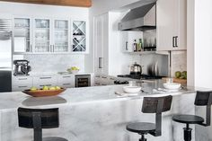 Fantastic kitchen features white cabinets adorned with black hardware paired with white marble ...
