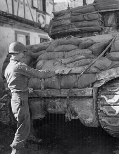 Corporal Arthur Garrett of the US 14th Armored Div adds a final flourish to cement filled sand bags on his Sherman tank. There is much debate as to the real protection gained by doing this & Gen.Patton was against it. He thought the added weight slowed the tank & therefore lost it's tactical advantage- speed/maneuverability. It certainly did provide a psychological comfort to the tank crews inside who used such improvised additions. Other crews added timbers & extra tank tracks outside the h...
