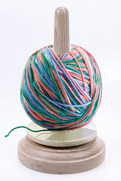 Easy to use. Just put the ball on the holder and the base rotates so you can pull the yarn in total comfort with no more tangles. Made of wood. Yarn not included.