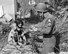 Italy October 6, 1943 An American soldier shares his rations with two hungry Italian waifs.