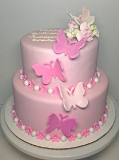 Butterfly birthday. 2 tier round cake covered in pink marshmallow fondant. Pink flower blossoms and pearl chocolates around the base of each tier. Pink fondant butterflies up the front of the cake with small gumpaste flower topper on the top.