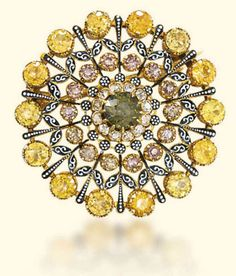 A ZIRCON AND ENAMEL REVIVALIST PENDANT/BROOCH, BY CARLO GIULIANO The openwork medallion with a central green zircon within a border of diamonds and concentric rings of yellow and brown zircons, accented with black and white piqué enamel, a folding pendant loop to the top, mounted in gold, circa 1890, 3.3cm wide With maker's initials 'C.G.' for Carlo Giuliano