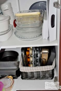 Tips on organizing kitchen cabinets. Put baking sheets/muffin tins in a basket. Duhh, why didn't I think of that?