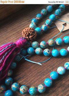 blue jasper hand knotted mala beads, pink thread multi tassel for nurture, meditation, yogi fashion, boho, prayer beads, rudraksha guru bead  Made with love. Hand knotted.  8 mm beads, perfect size for meditation  The unique artistry of Jasper is that of Nature itself - golden sunshine, a nighttime sky, poppy fields or a deep green forest, desert sands, the undulating ocean, red rock canyons, sweeping mountains. Each stone is a masterpiece of the Creator, bold and primitive in style, solid…