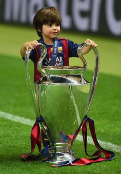 Milan Pique son of Gerard Pique of Barcelona poses with the trophy after the UEFA Champions League Final between Juventus and FC Barcelona at Olympiastadion on June 6, 2015 in Berlin, Germany.