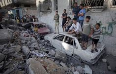 AP Photo/Khalil Hamra Palestinians gather at the destroyed home of the Ghannam family. Five members of the family were killed after an Israeli missile strike hit their home early morning in the Rafah refugee camp in the southern Gaza Strip.