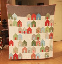 from cluck cluck sew. I love house quilts, especially when a village is the picture. I wonder why the upper part of the quilty picture isn't sky-colored?