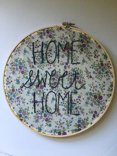 """Home Sweet Home Hand Embroidered Hoop. """"Home Sweet Home"""" hand stitched on to a lovely vintage fabric with purple and blue floral bouquets. One of kind, handmade by me, probably while relaxing on my porch swing. It is sure to be a standout addition to your home decor. ✒︎ M E A S U R E M E N T S ~ 10"""" hoop ✒︎ M A T E R I A L S ~ grey thread ~ vintage floral fabric ✒︎ S H I P P I N G ~ allow 3-8 days till shipment ✒︎ S H O P ~ See what else we have in stock here etsy.com/shop/WrightandCo ✒︎ F O…"""