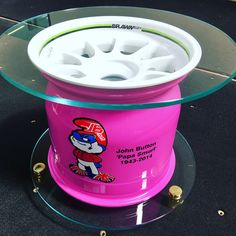 A tribute to Jenson Button's Dad who passed away in 2014, and also Jenson's Wold Championship victory in 2009 with Brawn GP.  The wheel has been professionally powder coated in White, and then the inner rim professionally sprayed in pink and then lacquered over. We have used 10mm Low Iron ultra clear Toughened glass for the top and the plinth, with solid steel polished bronze presentation feet.