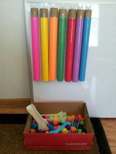 Our DIY color sorting game. Cardboard tubes, colored paper, tape around colored paper to protect and easy cleaning, colored pom poms, kids tweezers,  I used command hooks to hold it to the board.