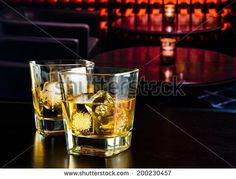 whiskey glasses with ice in a lounge bar on wood table - stock photo