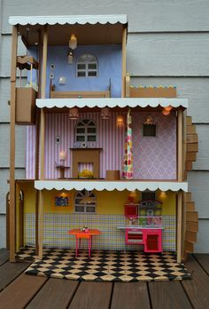 I made a barbie house like this when I was a kid. Just a cardboard box, wallpaper samples (ask Lowes or Home Depot to give you their old books) carpet samples (again ask Lowes or Home Depot for old samples.) Fill with your doll furniture or make your own.