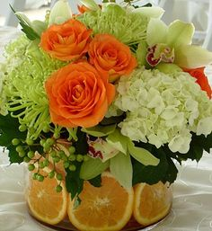 Citrus Centerpieces | In addition to fresh and colorful Spring flowers, I love how fruit slices are incorporated into these bright and sunny centerpieces.