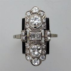 Art Deco enamel and diamond plaque ring, the pierecd oblong panel w/ scalloped ends, pavé set w/ graduated brilliant-cut diamonds, centred by 2 baguette-cut diamonds, flanked by 2 old brilliant-cut diamonds estimated to weigh a total of approx. 0.6 carats, all millegrain set to a platinum mount w/ black enamel detail to the sides, to a pierced cheniered gallery, gross weight 3.7 grams, circa 1930. (hva)