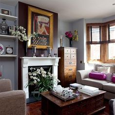 living room with gray walls, painted fireplace, big modern art, dark wood antiques, wooden blinds, big flowers
