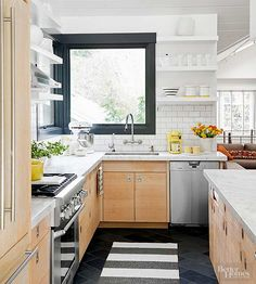 White subway tile sets a vintage stage for classic marble countertops and modern cabinets equipped with flat-planed slab doors. Dark tile floors and black-painted window trim underscore the kitchen's progressive attitude, while open storage and accessories give a nod to days gone by.
