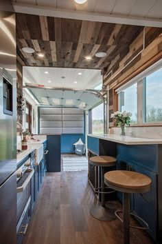 This luxury custom tiny house features wood accents, a wet bar, and a garage door in the living room.