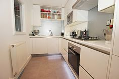 Small white kitchen in an L-Shape kitchen layout with all-white laminate cabinetry and worktop.