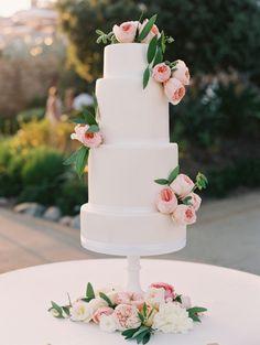 White four tier wedding cake topped with pink peonies: http://www.stylemepretty.com/2016/12/14/pink-laguna-beach-wedding/ Photography: Valentina Glidden - http://valentinaglidden.com/