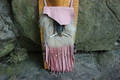 This large medicine bag is designed with Pink Deer Skin Leather and adorned with all things coyote, including fur, teeth, and claws. An agate Arrowhead decorates the inner flap, and beaded with Amethy