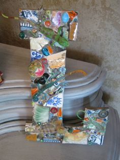 """Mosaic letter """"L"""" with lizards in orange, green and blue, mosaic art."""