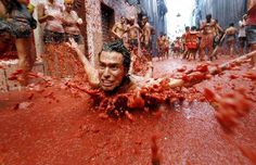 A man dives into a puddle of tomato pulp. La Tomatina in Bunol, Spain