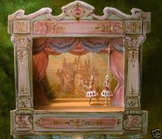 Dollhouse or Antique Doll accessory.... Artisan created Victorian tabletop theatre --- inspired by the old antique toys of the late 1800's, by Jill Dianne. Hand-painted in soft pinks and minty greens with metallic gold accents . Sits on a beautiful Bespaq console table embellished with Jill Dianne's hand-sculpted roses and painted in a coordinating minty green and metallic gold. Includes two tiny mechanical puppets.