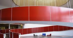 Image description: The Red Ramp at the Ed Roberts Campus, which descends from the second to the first floor in a large spiral and seems to...