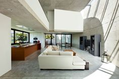 Modern concrete living room with large white sofa in open concept design