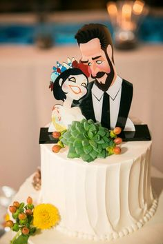 Delightful caricatures of the bride and groom are highlighted by sprigs of hypericum and succulents at Ivy and Brian's Lake House Inn wedding: Nicole Leigh Photography.