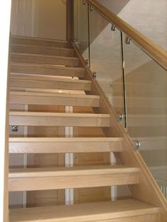 Oak staircase with open risers and glass balustrading by Merrin Joinery