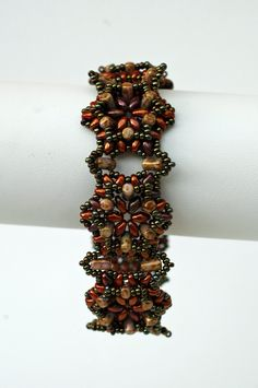 In this stunning beadwoven bracelet, you will surely make an elegant statement! I used Japanese seed beads, Czech Superduo beads and Rulla beads in metallic green, chestnut brown, alabaster amber colors. The bracelet is woven on special Fireline beading thread so its strong but soft and flexible. It fills very nice against the skin. Bracelet is closing with antiqued bronze tone lobster claw clasp.  Bracelet is 7 1/2 inches long and about 1inch in width . It has 1 1/2 inches extender chain to…