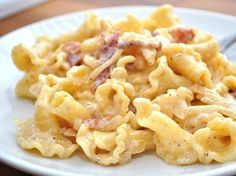 Gouda Stovetop Mac and Cheese      1 pound Campanelle Pasta     5 slices Bacon     1 whole Sweet Onion, Chopped Finely     1 cup Heavy Cream     1 cup Shredded Gouda Cheese     1 pinch Salt To Taste     1 pinch Black Pepper To Taste