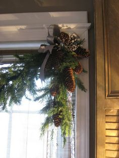 pine cone cluster, greenery swag and ribbon for family room windows.