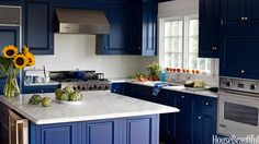 White Carrara marble countertops, finished with a traditional ogee edge, set off cabinets painted Benjamin Moore's Champion Cobalt in this Bridgehampton, New York, kitchen.