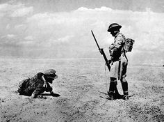 A wounded German officer, found in the Egyptian desert during the first two days of a British offensive, is guarded by a sentry while awaiting backup, on November 13, 1942. (AP Photo) #World War II: The North African Campaign - In Focus - The Atlantic