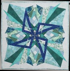 """Marla Head Whalen  This is my quilt """"Fractured"""", approximately 40 x 40 inches. It's ironic that I own a shelf full of Dover books, but this was created from an image in a Dover sampler! It's number 476782-011 from the Terrific Triangles book.  It was really fun enlarging the image and figuring out how to interpret the design in fabric!"""