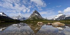 Glacier National Park's majestic mountain peaks are reflected on a lake's surface