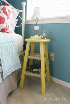 Repurpose an old stool into a little night table. Note the DIY rope shelves.